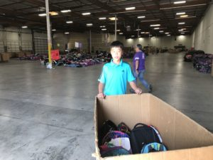 GATA member delivering backpacks to Family Giving Tree warehouse